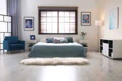 Interno della stanza con i ciechi comodi di finestra e del letto matrimoniale fotografia stock libera da diritti