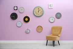 Interno della stanza con molti orologi differenti sulla parete fotografie stock