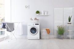 Interno della stanza di lavanderia con la lavatrice fotografie stock