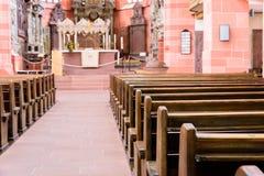 Interno di bella vecchia chiesa cattolica da sotto con il pavimento di marmo, i banchi di chiesa di legno e la luce che scorre su Fotografie Stock