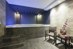 Interno di una stazione termale dell'hotel con il bagno della Jacuzzi con le luci ambientali Fotografia Stock Libera da Diritti