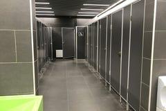 Interno di una toilette pubblica con le porte aperte nelle stalle nei toni grigio scuro immagine stock libera da diritti