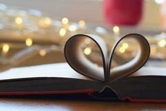 Interno domestico accogliente con il libro, il cuore e le luci blured immagini stock libere da diritti