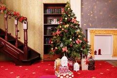 Interno domestico accogliente, con l'albero di Natale e la decorazione del nuovo anno fotografia stock libera da diritti