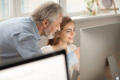 Interno envelhecido do treinamento do mentor que explica o trabalho que aponta no computador foto de stock royalty free