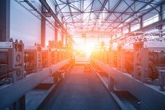 Interno industriale della fabbrica con la linea del trasportatore per il rotolo del metallo che si forma come fondo astratto di i immagine stock libera da diritti