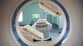 Interno irreconocible que miente en MRI, tomograph, escáner, moviéndose a y desde la cámara Lanzamiento del resbalador