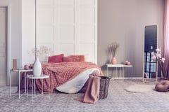 Interno luminoso della camera da letto con il grande letto comodo con i cuscini arancio sporchi e la coperta accogliente fotografie stock libere da diritti