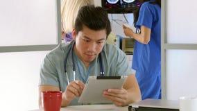 Interno médico na sala de estar do hospital usando o PC da tabuleta  video estoque