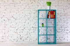 Interno in mattone bianco con uno scaffale per libri Immagini Stock