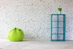 Interno in mattone bianco con uno scaffale per libri Immagine Stock