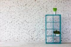 Interno in mattone bianco con uno scaffale per libri Fotografia Stock