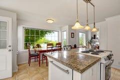 Interno moderno bianco luminoso della cucina con l'isola e l'area pranzante Fotografia Stock Libera da Diritti