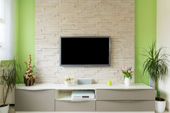 Interno moderno del salone - la TV ha montato sul muro di mattoni con lo schermo nero fotografia stock