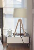 Interno moderno della camera da letto con la lampada e la sveglia di legno sulla tavola Fotografia Stock Libera da Diritti