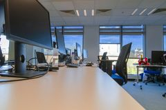 Interno moderno vuoto dell'ufficio dello spazio aperto Scrivanie vuote e computer e monitor spenti contro luce solare dalle fines fotografia stock