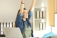 Interno satisfecho que aumenta los brazos en la oficina Imagen de archivo