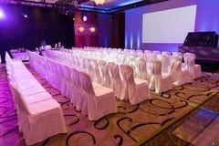 Interno vuoto della sala per conferenze o della stanza di seminario di lusso con lo schermo del proiettore, sedie bianche Fotografie Stock