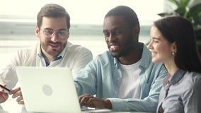 Internos de ensino de sorriso do mentor afro-americano que apontam no portátil vídeos de arquivo