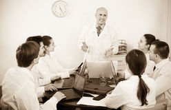 Interns and professor at hospital meeting Royalty Free Stock Images