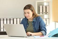 Internuje pracującego z laptopem online przy biurem Fotografia Stock