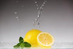Intero e limone affettato del ‹del †del ‹del †in uno spruzzo di acqua Fotografie Stock