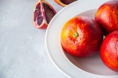 Intero maturo fresco e fette di arance sanguinelle in un piatto su un whi fotografia stock
