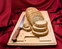 Intero pane affettato del granulo su legno Fotografia Stock