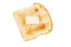 Intero pane tostato del grano con un picchiettio di burro immagine stock libera da diritti
