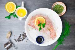 Intero pesce persico organico crudo del pesce sui cubetti di ghiaccio in piatto bianco su un fondo scuro della tavola Vista super fotografia stock libera da diritti