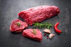 Intero pezzo di filetto con le bistecche e le spezie o pronta da cucinare Immagine Stock Libera da Diritti