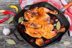 Intero pollo arrostito in leccarda con aglio, peperoncino rosso fotografia stock