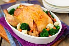 Intero pollo arrosto farcito con pane e formaggio serviti con la st fotografia stock