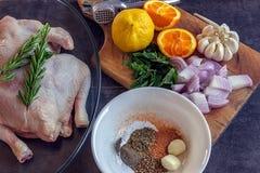 Intero pollo crudo con la cipolla, l'aglio, il limone e l'arancia tagliati fotografia stock libera da diritti