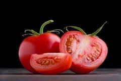Intero pomodoro rosso con la fetta Fotografia Stock