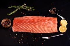 Intero raccordo di color salmone con i rosmarini, limone, granelli di pepe, con una forchetta e un cucchiaio immagine stock