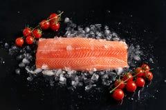 Intero raccordo di color salmone crudo su ghiaccio scheggiato sui pomodori ciliegia neri di spirito una h del fondo su un ramosce fotografie stock libere da diritti