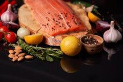 Intero raccordo di color salmone su un bordo di legno con un ramoscello dei rosmarini, dei pomodori ciliegia, delle cipolle, dell fotografia stock libera da diritti