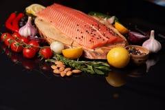 Intero raccordo di color salmone su un bordo di legno con un ramoscello dei rosmarini, dei pomodori ciliegia, delle cipolle, dell immagini stock libere da diritti