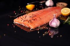 Intero raccordo di color salmone su un fondo scuro, spruzzato con i granelli di pepe multicolori con aglio, rosmarini ed il limon fotografia stock libera da diritti