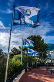 Interplay of blue flags on sky background in Monaco. Combination of blue tissue and blue sky in Monaco Stock Image