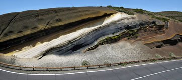 An Interplay of Colors along Tenerife roads. The pattern of layers originated from different eruptions. Phonolytic white layer is pumice fragments, black is Royalty Free Stock Images