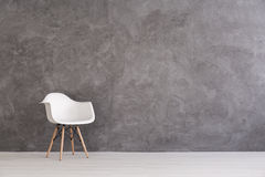 Interplay of different textures. White plastic chair on a background of a gray concrete wall Royalty Free Stock Image