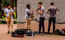 Interprète de rue à Amsterdam avec le mur de réflexion, jouer violine et saxophon images libres de droits