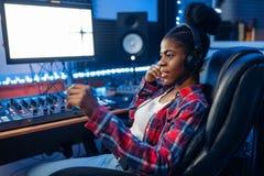 Interprète féminin au moniteur, studio d'enregistrement images stock