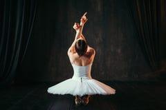 Interprète féminin de ballet classique s'asseyant sur le plancher photo libre de droits