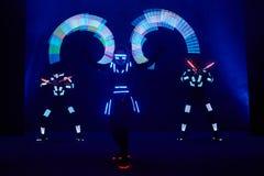 Interprétation d'exposition de laser, danseurs dans les costumes menés avec la lampe de LED, interprétation très belle de boîte d images stock