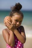 Interpréteur de commandes interactif de conque de fixation de fille à côté de son oreille. Photographie stock libre de droits