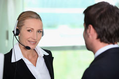 Interpreter with client. Interpreter wearing head-set stood with client Royalty Free Stock Image