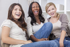 Interracial Beautiful Women Friends Laughing. Interracial group of three beautiful young women friends at home sitting together on a sofa smiling and having fun Royalty Free Stock Photos